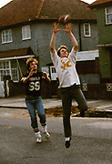 Teenagers play American football in the street, London, UK, 1983