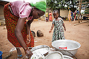 Christine Koné, 26, does dishes outside her home in the town of Katiola, Cote d'Ivoire on Friday July 12, 2013. Christine underwent FGM as a child and now suffers from incontinence. She says she would never allow her daughter to undergo the procedure.