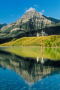 Prince of Wales Hotel reflected in Upper Waterton LAke with the Canadian Rockies in the background.<br /> Waterton Lakes National Park<br /> Alberta<br /> Canada
