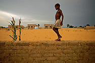 A young boy walks atop a brick wall surrounding a health clinic in Niger.  Due to continually shifting sands and other environmental factors, the clinic has never been able to officially open.