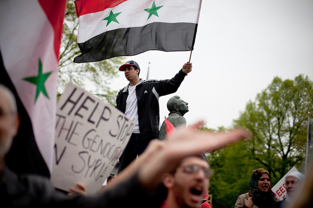 A young man waves Syrian flag during a rally to raise awareness to the situations in Syria and Libya on Boston Common yestrerday.