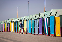 © Licensed to London News Pictures. 22/04/2019. Brighton and Hove, UK. A man walks his dog past multi-coloured beach huts on the Western Esplanade at Hove, West Sussex. Most of the UK is enjoying record breaking high Easter weekend temperatures. Photo credit: Peter Macdiarmid/LNP