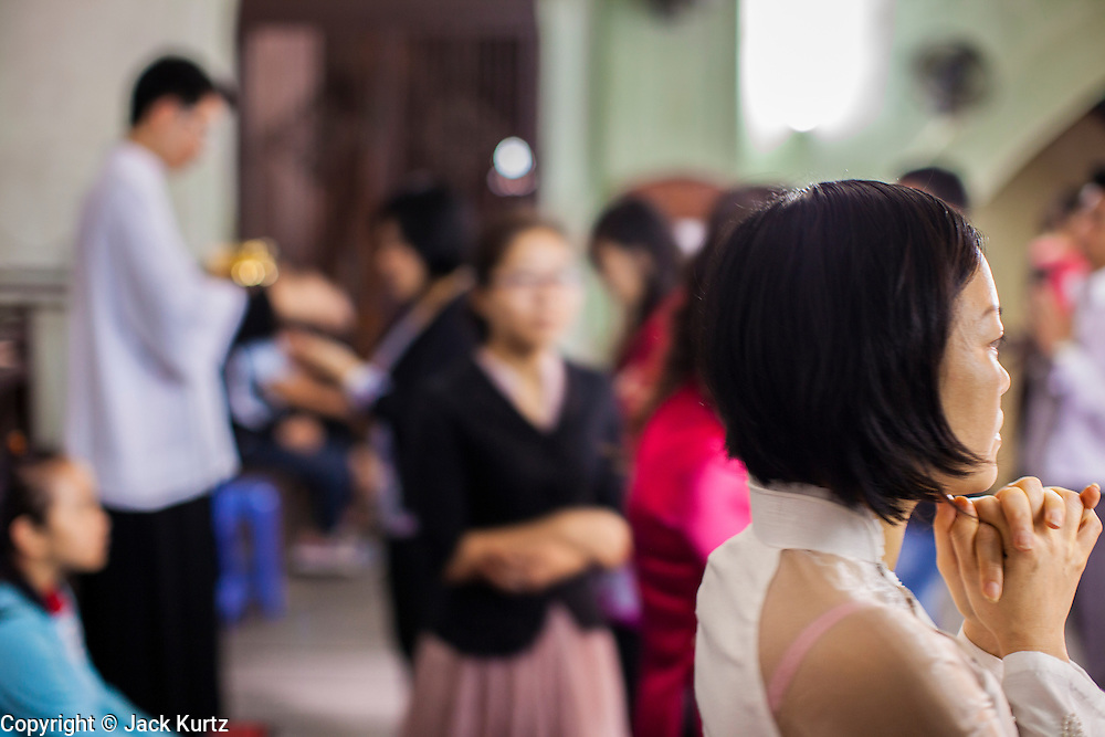08 APRIL 2012 - HANOI, VIETNAM:   A woman prays after receiving Holy Communion during Easter Sunday mass in St. Joseph Cathedral in Hanoi, Vietnam. St. Joseph Cathedral in Hanoi is the seat of the Roman Catholic Archdiocese of Hanoi and is one of the most important Catholic churches in Vietnam. It was built in 1886 and is especially crowded on religious holidays, like Easter. The church holds three Easter masses on Easter Sunday morning. There are more than 5.6 million Roman Catholics in Vietnam, nearly 7% of the population. Catholicism came to what is now Vietnam with Portuguese missionaries in the 16th Century, but it wasn't until the arrival of French missionaries and later colonial authorities that Catholicism became a part of Vietnamese religious life.     PHOTO BY JACK KURTZ