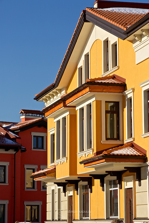 "Architectural details of residential real estate development project ""Italian Village"" in Kyiv, Ukraine. Exterior view of villeta with yellow walls in the sunset sunlight."