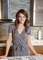 Portrait of beautiful young female with tile samples on kitchen counter