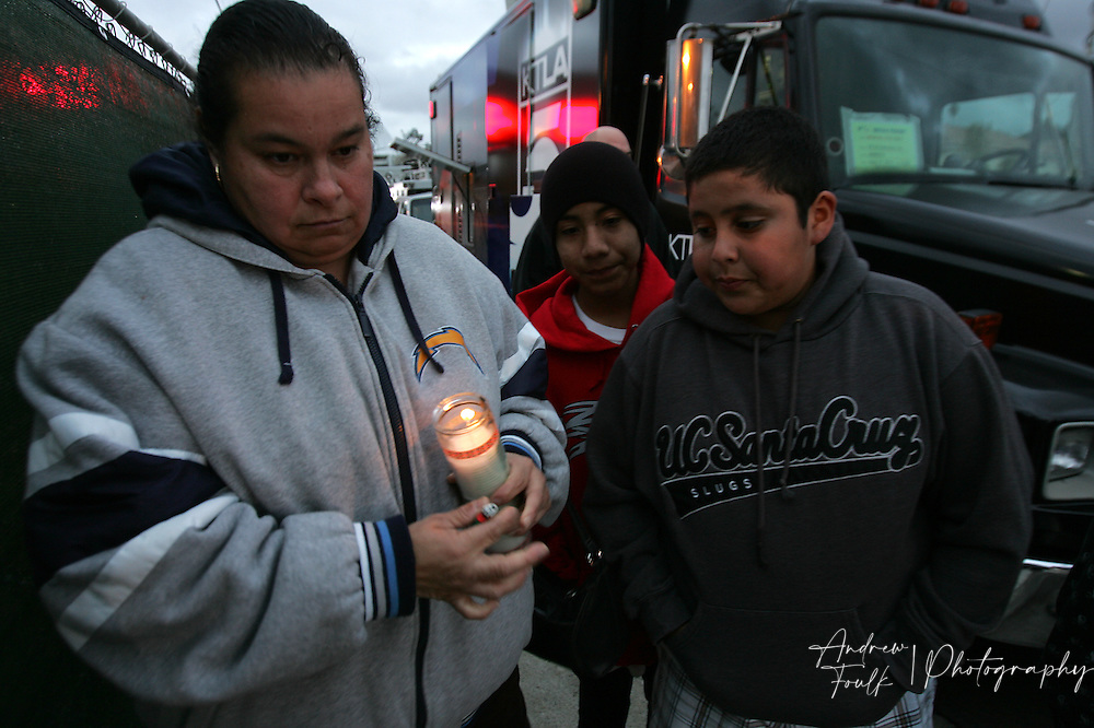 /Andrew Foulk/ For the North County Times/  .Silvia Murguia, of Vista, holds a candle before placing it near photo of  Amber Dubois during a Vigil to remember the fourteen year old at Escondido High School Monday night.
