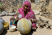 Indian woman in traditional Rajasthani clothing works at home painting clay water pots in Nimaj village, Rajasthan, India RESERVED USE - NOT FOR DOWNLOAD -  FOR USE CONTACT TIM GRAHAM