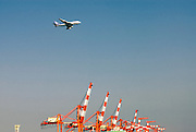 An All Nippon Airlines plane flies over cranes used for loading cargo onto ships in Tokyo Bay, Tokyo, Japan.