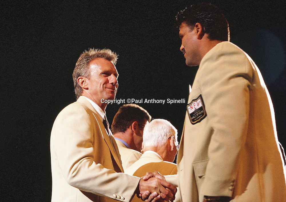 Former San Francisco 49ers quarterback Joe Montana shakes hands with Cincinnati Bengals offensive lineman Anthony Munoz during the NFL Pro Football Hall of Fame civic dinner held on the weekend Montana was inducted into the NFL Pro Football Hall of Fame on July 28, 2000 in Canton, Ohio. (©Paul Anthony Spinelli)