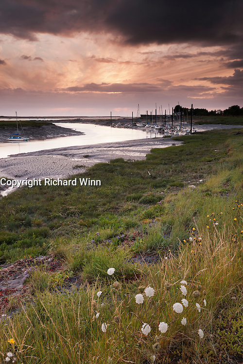 The mouth of the River Brue, as it meets the Parrett at  Burnham on Sea, with the sun shining through storm clouds above.