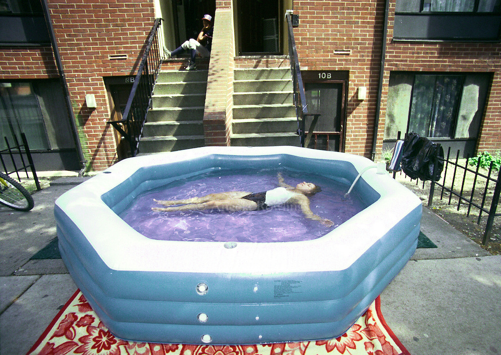 A woman floats in a wading pool in front of her house in the Villa Victoria neighborhood of the South End in Boston.