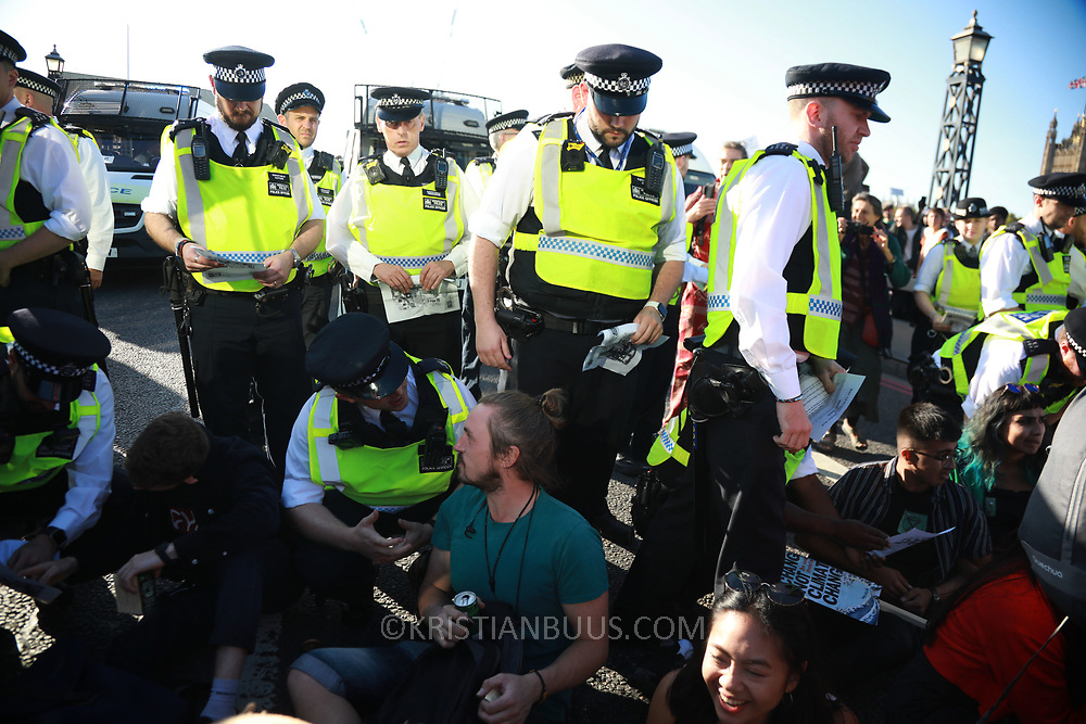 Tens of thousands took to the streets in Central London taking part in the the Global Climate Strike, September 20th 2019, London, United Kingdom.  For a short while Lambeth Bridge was occupied by sitting protesters, most of them teenagers. The Police quickly cleared the bridge and opened it up to traffic again. The day of strike for the climate was a global event with millions taking part across the globe. The strike was inspired by Greta Thunberg, a Swedish school girl who started the first school strike for the climate. Her action inspired school children across the world to go on strike demanding radical climate change policies to save their future. On September 20th adults aand children alike went out on strike to demand radical political change and climate justice. The day included speeches and a march through central London.