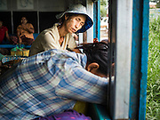 26 OCTOBER 2015 - YANGON, MYANMAR: Passengers sleep on the Yangon Circular Train. The Yangon Circular Railway is the local commuter rail network that serves the Yangon metropolitan area. Operated by Myanmar Railways, the 45.9-kilometre (28.5 mi) 39-station loop system connects satellite towns and suburban areas to the city. The railway has about 200 coaches, runs 20 times daily and sells 100,000 to 150,000 tickets daily. The loop, which takes about three hours to complete, is a popular for tourists to see a cross section of life in Yangon. The trains run from 3:45 am to 10:15 pm daily. The cost of a ticket for a distance of 15 miles is ten kyats (~nine US cents), and for over 15 miles is twenty kyats (~18 US cents).    PHOTO BY JACK KURTZ