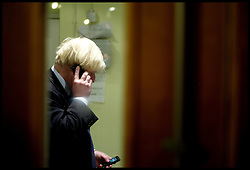 London Mayor Boris Johnson on his mobile phone with visiting  West Hampstead, London,  United Kingdom. Thursday, 28th November 2013. The Boy's Club House offers mentoring, activities, careers advice in the Jewish Community. Picture by Andrew Parsons / i-Images