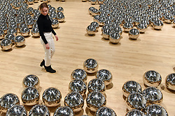 "© Licensed to London News Pictures. 25/09/2018. LONDON, UK. A gallery staff member walks through ""Narcissus Garden"", 1966-, by Yayoi Kusama. Preview of ""Space Shifters"" at the Hayward Gallery, an exhibition which features artworks by 20 leading international artists that disrupt the visitor's sense of space and alter their perception of their surroundings.  The show runs 26 September to 6 January 2019.  Photo credit: Stephen Chung/LNP"