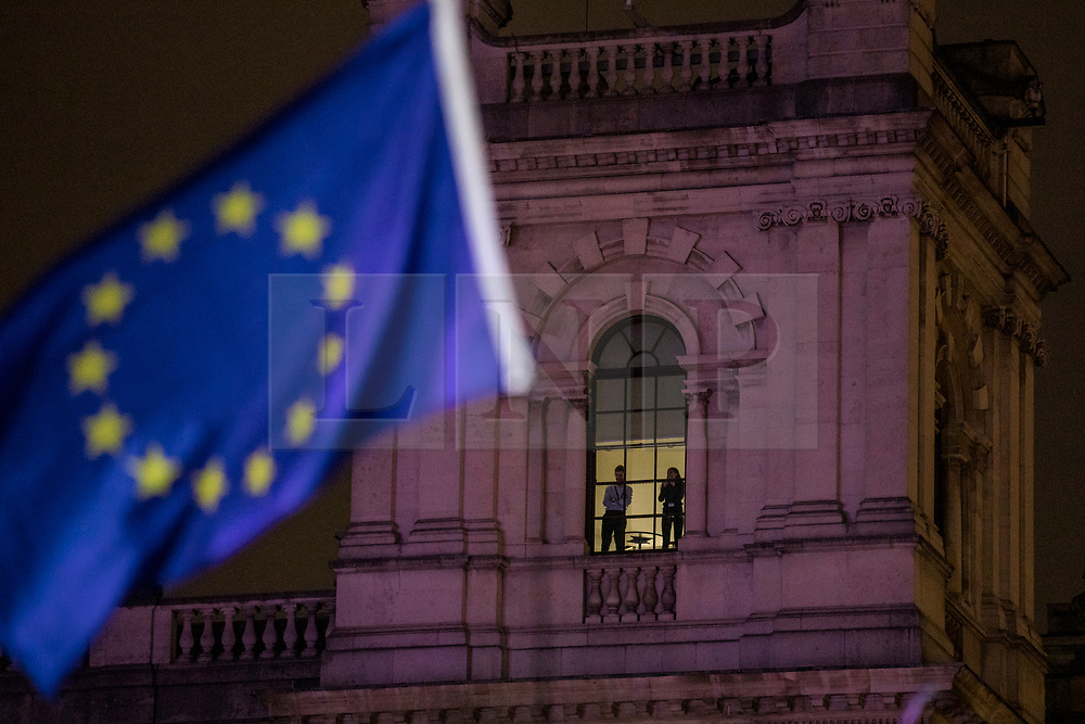 © Licensed to London News Pictures. 15/01/2019. London, UK. Two people watch from the top of a government building on the corner of Parliament Square as thousands gather for a People's Vote rally. MPs will vote on Prime Minister Theresa May's Brexit deal this evening. Photo credit: Rob Pinney/LNP