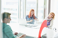 Happy businesspeople sitting at desk in creative office