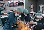 "At an early-morning procedure at Shadyside Hospital in Pittsburgh, Anthony M. DiGioia (center) uses HipNav, a computerized navigation system he developed in collaboration with Carnegie Mellon's Center for Medical Robotics and Computer-Assisted Surgery, to replace the hip of a 50-year-old Pittsburgh man. Aligning the new hip properly, DiGioia explains, is necessary to avoid surgical complications. Here DiGioia, a former robotics student, uses the intra-operative guidance system and a simple ""aim and shoot"" interface to emplace the new hip. Robo Sapiens page 177."