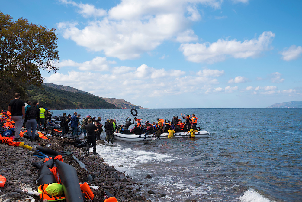An inflatable boat filled with refugees and other migrants arrives on the north coast of the Greek island of Lesbos, where it is met by volunteers and photographers. More than 500,000 migrants have crossed from Turkey to the Greek islands so far in 2015.