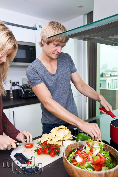Man cooking with woman in kitchen