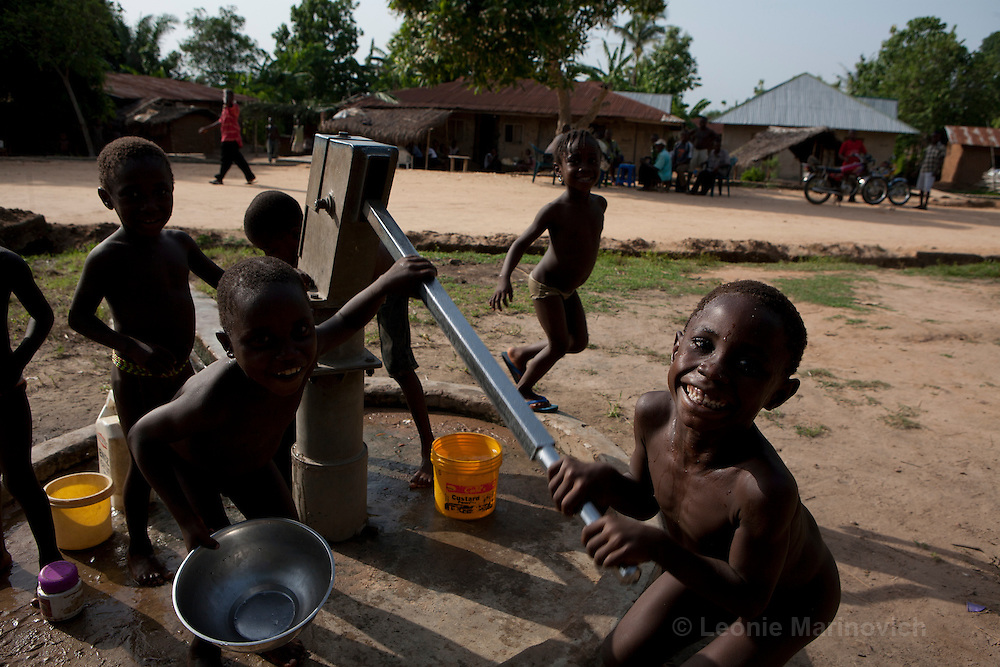8 April 2010. Ekpeti, Cross River State, Nigeria. Kids fetching water from the bore hole hand pump.