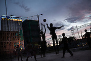 Teenegars playing volleyball at sunset inside one of the many construction yards of Diamond Island, the brand new commercial and residential area in Phnom Penh, Cambodia.<br /> The LSS2 dam could potentially generate a fifth of the power Cambodia is likely to need by 2018 but the effects on the environment are devastating.