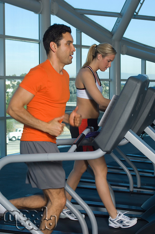People Exercising on Treadmills in Health Club
