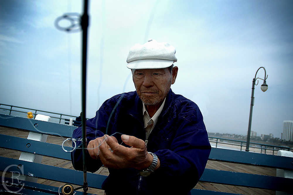 A fisherman fixes his line off the Santa Monica Pier.