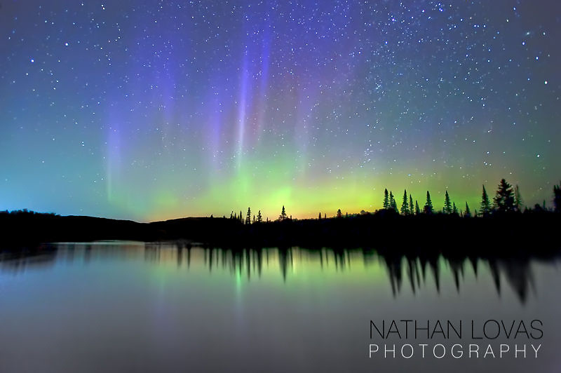 Aurora borealis over northern Minnesota lake;  Grand Portage, Minnesota.