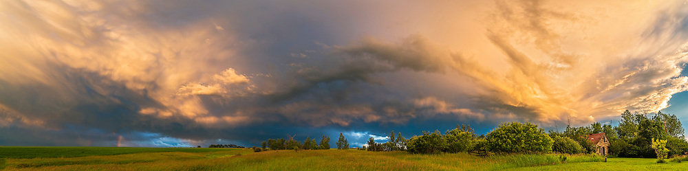 A cloudscape of a thunderstorm and rainbow fragment in the light of the low Sun from home in southern Alberta, July 3, 2016. A wonderful sky of colours, shades, and shapes. Certainly a Turneresque sky.<br /> <br /> This is a panorama stitch of 8 segments with the Sigma 20mm lens and Nikon D750.