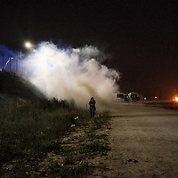 Tear gas covers a journalist, when he was reporting the clash between french police and the migrants.