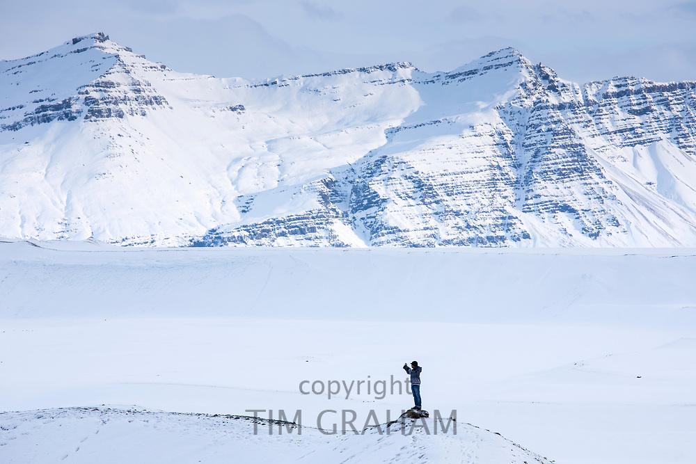 Tourist taking selfie photograph using smartphone at Jokulsarlon glacial lagoon, Vatnajokull National Park,  South East Iceland