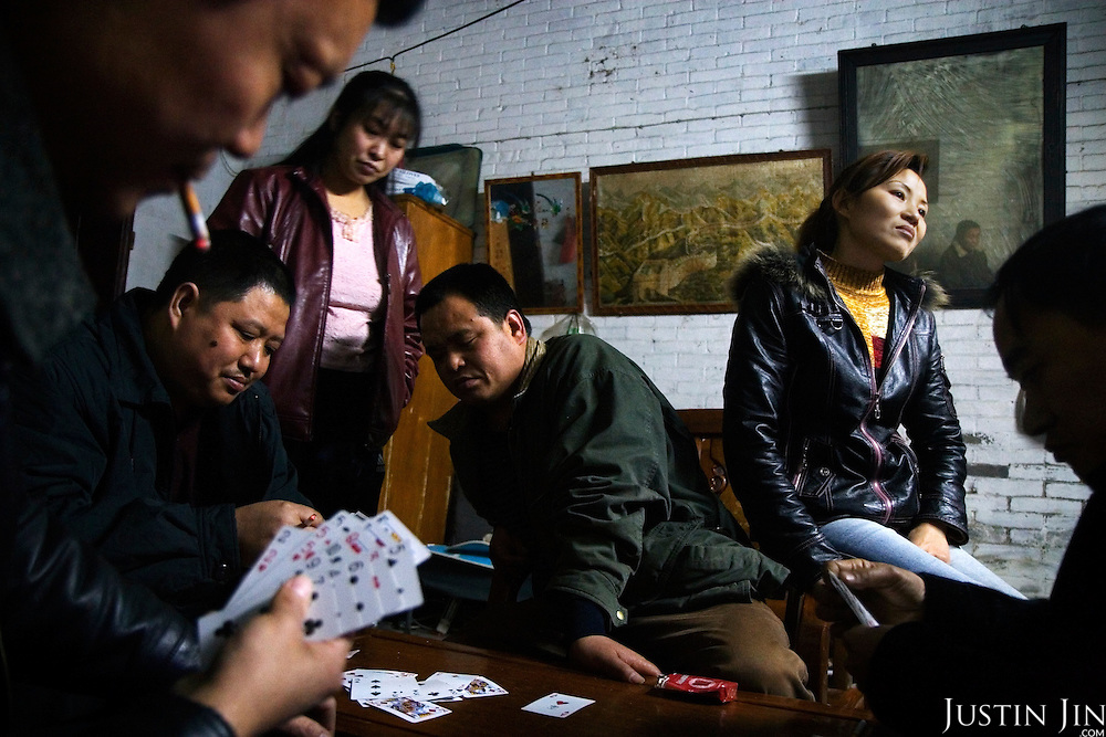 "Factory boss Mr Huang (top left corner) plays cards with fellow bosses and their wives at his home in Zhongshan city, China. .This picture is part of a photo and text story on blue jeans production in China by Justin Jin. .China, the ""factory of the world"", is now also the major producer for blue jeans. To meet production demand, thousands of workers sweat through the night scrubbing, spraying and tearing trousers to create their rugged look. .At dawn, workers bundle the garment off to another factory for packaging and shipping around the world..The workers are among the 200 million migrant labourers criss-crossing China.looking for a better life, at the same time building their country into a.mighty industrial power."