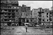 Beyrouth, Liban.13-03-84. Ai?n-el-Remaneh, quartier chre?tien de la capitale libanaise, un enfant rejoint son habitation situe?e sur la ligne de de?marcation..©Herve? Merliac..Beirut, Lebanon march 13 1984. A child, taking shelter under an ombrella against the sun, walks back to his home in the christian area of Ai?n-el-Remaneh, on the Green line dividing east and west Beirut...©Herve? Merliac