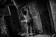 """Ketut's mother is unlocking the room where she has held her son since 2006.  """"He was very aggressive and stole a cow, then he started hitting me and even tried to kill his father, we had no choice but to chain him and lock him up"""". Bali, Indonesia.<br /> ©Ingetje Tadros"""