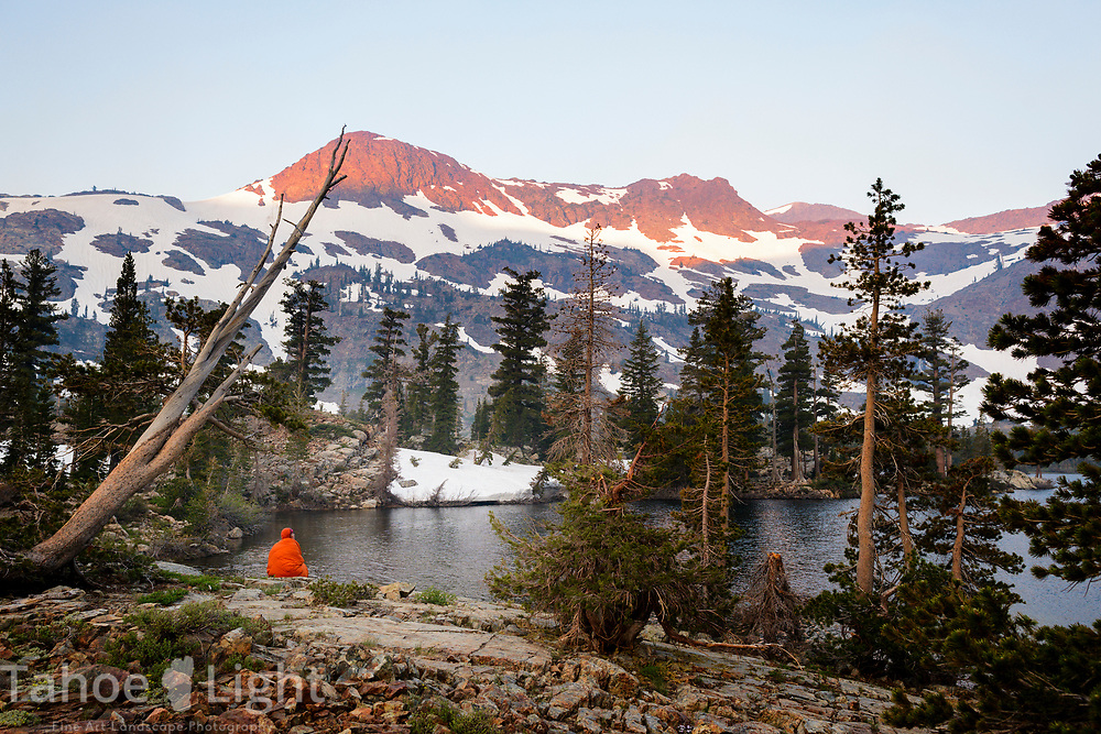 Backpacker watching the smoky sunrise at Honeymoon Lake in the Desolation wilderness hike in south lake tahoe
