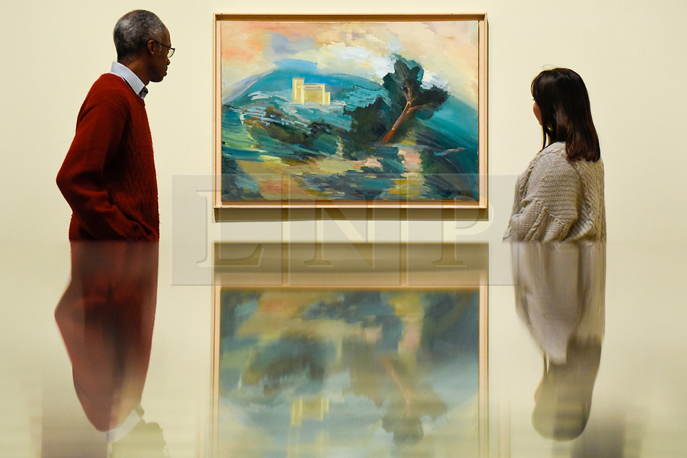 """© Licensed to London News Pictures. 19/11/2019. LONDON, UK. Staff members view a painting called """"Untitled (House in Menerbes)"""", after 1945, by Dora Maar. Preview of the first UK retrospective of Dora Maar (born Henriette Theodora Markovitch, 1907-97) whose photographs and photomontages became celebrated icons of surrealism.  Over 200 of her works are on display in a career spanning more than six decades at Tate Modern 20 November to 15 March 2020.  Photo credit: Stephen Chung/LNP"""