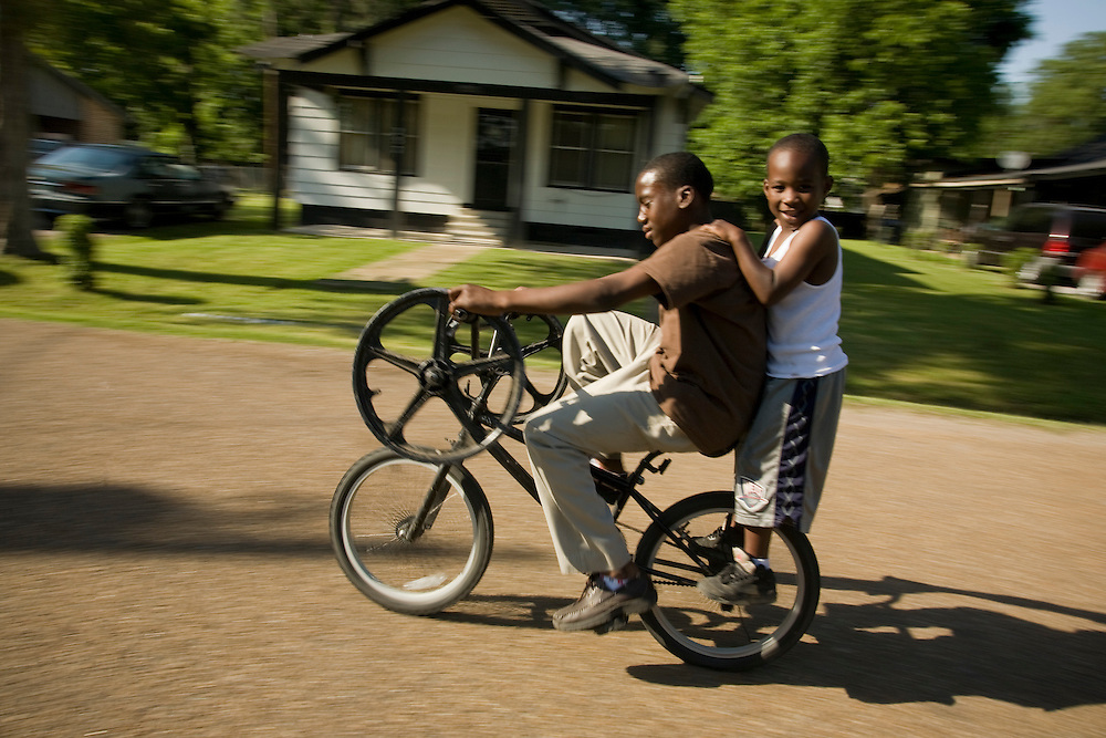 Jamaris Smith, 13, left, and Douglas Maddox, 6, ride through the streets of Jonestown, Miss., 2007.<br /> Photo by D.L. Anderson