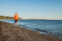 A yong man running on a beach in Discovery Park, Seattle, Washington, USA.