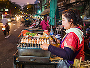 24 FEBRUARY 2016 - BANGKOK, THAILAND: A woman sells grilled Thai pork sausages from a cart in front of Pak Khlong Talat in Bangkok. Bangkok government officials announced this week that vendors in Pak Khlong Talat, Bangkok's well known flower market, don't have to move out on February 28. City officials are trying to clear Bangkok's congested sidewalks and they've cracked down on sidewalk vendors. Several popular sidewalk markets have been closed in recent months and the sidewalk vendors at the flower market had been told they would be evicted at the end of the month but after meeting with vendors and other stake holders city officials relented and said vendors could remain but under stricter guidelines regarding sales hours. The flower market is one of the best known markets in Bangkok and has become a popular tourist destination.       PHOTO BY JACK KURTZ