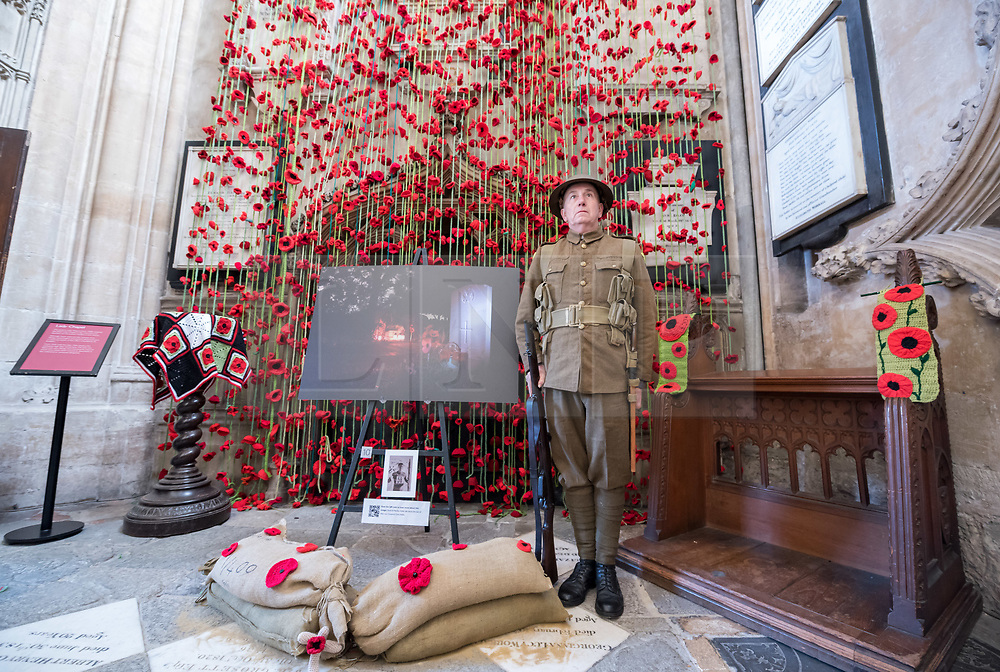 "© Licensed to London News Pictures. 27/10/2018. Bristol, UK. The Royal British Legion launch this year's Poppy Appeal, ""One thousand poppies, for one hundred years, for one million lives"" at Bristol Cathedral. Picture inside Bristol Cathedral of Somerset Light Infantry re-enactor DAVID HARRIS by a commemoration for Corporal Chris Addis who was killed in Bosnia in 1998. For the launch of the 2018 Bristol Poppy Appeal at 11am on 27 October, The Royal British Legion recreated a scene from the end of WW1 outside Bristol Cathedral on College Green, and Colonel Clive Fletcher-Wood read the war poem In Flanders Fields. They were joined by a Bugler and the Bristol Military Wives Choir who performed songs from their new album 'Remember'. Staff at MOD Filton filled 400 sandbags with eight tonnes of sand to build trenches and recreate 'Flanders Fields' and planted over 1000 waterproof poppies on College Green. Poppies and sandbags can be sponsored by individuals wanting to remember those who fought and died in conflict. There were re-enactors in WW1 uniform from Somerset Light Infantry (known as the West Country Tommys), as well as medics and nurses with equipment from the time. Bristol's own 'War Horse' (Buzz from Blagdon Horsedrawn Carriages) was on College Green behind the improvised barbed wire to represent the 350,000 horses that left Avonmouth for the frontline during WW1. There are also 10,000 knitted poppies on display both in and outside Bristol Cathedral following 'The Charfield Yarn Bombers' incitement to locals to get knitting to mark the occasion, with a display inside the Cathedral organised by Helen Date. Photo credit: Simon Chapman/LNP"