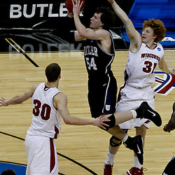 Mar 24, 2011; New Orleans, LA; Butler Bulldogs forward Matt Howard (54) shoots over Wisconsin Badgers forward Mike Bruesewitz (31) and forward Jon Leuer (30) during the second half of the semifinals of the southeast regional of the 2011 NCAA men's basketball tournament at New Orleans Arena. Butler defeated Wisconsin 61-54.  Mandatory Credit: Derick E. Hingle