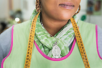 CASERTA, ITALY - 25 FEBRUARY 2015: A Holy Mary medallion and a cross are worn by a Nigerian immigrant woman and ex-sex worker that is now working at the New Hope tailor's shop in Caserta, Italy, on February 25th 2015.<br /> <br /> New Hope is an ethnic tailor's shop that makes a variety of colourful products working mainly african fabrics. The New Hope social cooperative, founded in 2014, promotes a training workshop for your immigrant women, many of which have children, that want to integrate in Italian society.