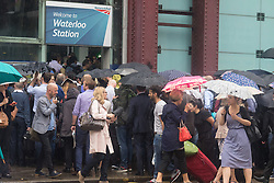 Waterloo Station, London, June 23rd 2016. Commuters face severe delays at London's Waterloo Station as bad weather causes power failures across the rail network. PICTURED: Passengers try to cram into one of the entrances of Waterloo station as the rain pours down on them.