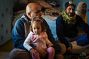"3 year-old Mariam sits with her father Alaa inside a house in Baharka camp. As Arabs in Iraqi Kurdistan Mahmoud feels that they are isolated and discriminated against. ""The Kurds say they are not responsible for us, we are Arabic so we should go to Baghdad for our health care,"" he explains."