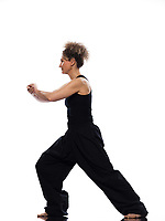 mature woman praticing tai chi chuan in studio on isolated white background