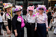 """New York, NY - April 16, 2017. Four women wearing hats that incorporate pink pussy hats into their designs  at New York's annual Easter Bonnet Parade and Festival on Fifth Avenue. The women also wear pink tags that read """"Purr-sist"""", """"Not for Grabs"""", """"Resist""""' and """"Resurrect."""""""