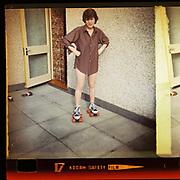 Girl in a man's shirt, on roller skates, London, UK, 1981
