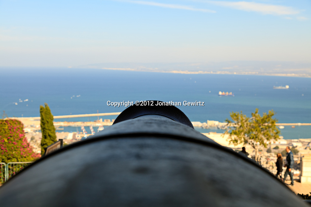 The view along the barrel of an ancient Ottoman cannon near Kaiser Wilhelm's Obelisk on the summit of Haifa's Mount Carmel. Haifa's port and harbor are visible in the distance. WATERMARKS WILL NOT APPEAR ON PRINTS OR LICENSED IMAGES.