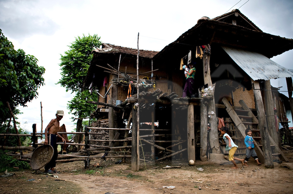 Traditional architecture of a Reungao ethnic tribe house. Kids are playing in the yard while the mother stands on the stilt deck. Kontum plateau, Pleiku area, Vietnam, Asia